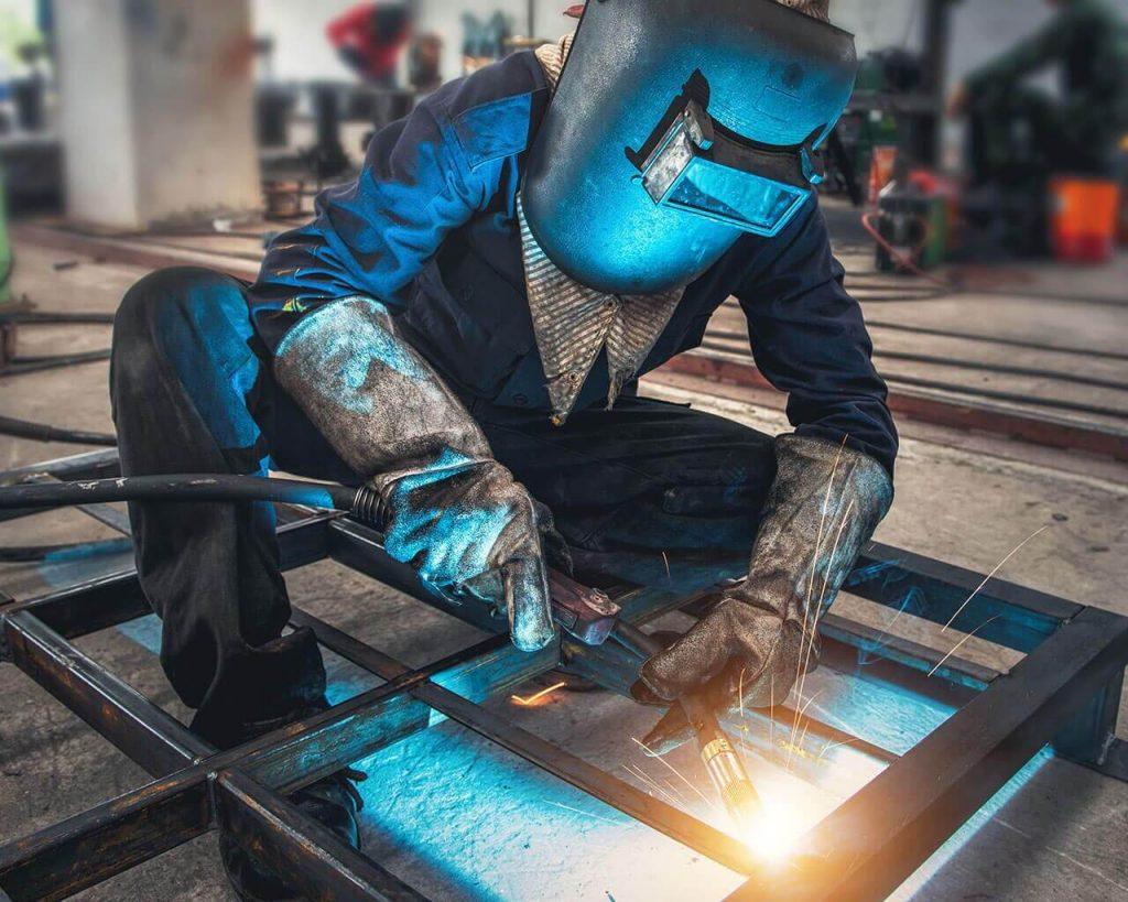 Зварювальник зварює металевий виріб