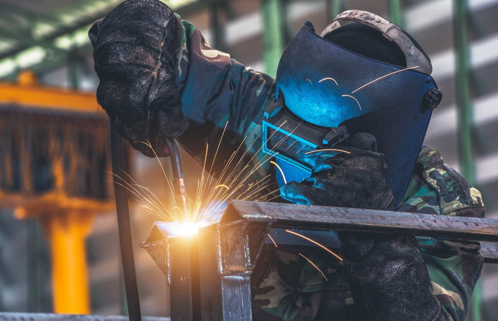 Зварювальник виготовляє металеву конструкцію
